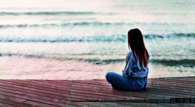 Una mujer sentada a la orilla del mar